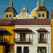 Colorful buildings and church domes in the Plaza de la Aduana, Old City, Cuidad Vieja, Cartagena, Colombia.