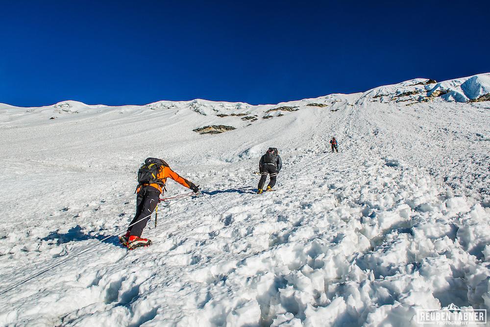 Three climbers make their way up the main ice wall, leading to the summit of Island Peak, Nepal.