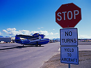 Grumman Goose used by the State of Alaska for Fish and Wildlife Protection crossing road at Ted Stevens International Airport and Lake Hood, Anchorage, Alaska.