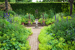 Mrs Winthrop's Garden at Hidcote Manor with Alchemilla mollis, aconitums, delphiniums and cordylines in terracotta pots. Sundial