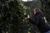 Michelle B. checks for homeless residents along a freeway embankment during the survey.