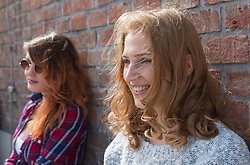 Two women leaning in front of brick wall, Munich, Bavaria, Germany