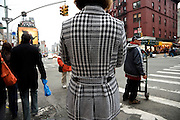 woman standing on a corner looking West out over Canal Street in NYC