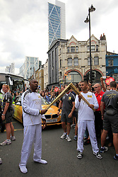 © Licensed to London News Pictures. 21/07/2012, London, UK.  Rapper, songwriter and record producer, Dizzee Rascal in his socks after discarding his trainers, left, hands over the London 2012 Olympic Torch flame to Mahboobur Rahman at Shoreditch in London during the Olympic Torch Relay, Saturday, July 21, 2012. Photo credit : Sang Tan/LNP