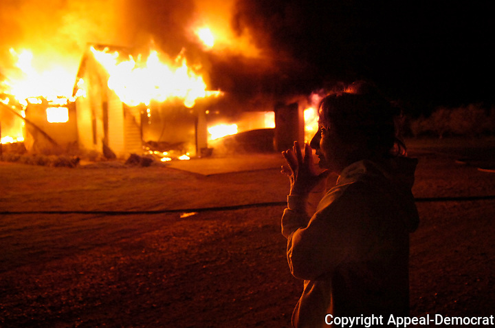 """Eva Woodard watches her house on Pass Road burn, Thusday, December 11,2008 in Sutter County. """"My daughter comes home from college tomorrow"""" said Woodard."""
