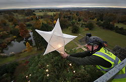 © Licensed to London News Pictures. 15/11/2016. Ardingly, UK. Steven Robinson, Nature Warden at Wakehurst Place, adjusts the star on top of the tallest Christmas tree in the UK. Every year for the last 24 years teams of arboriculturists climb the 110 ft [33 metres] redwood to string up the 1800 LED Christmas lights. The giant tree can be seen for miles around and acts as an unofficial beacon to pilots landing at nearby Gatwick airport over the festive period.  Photo credit: Peter Macdiarmid/LNP