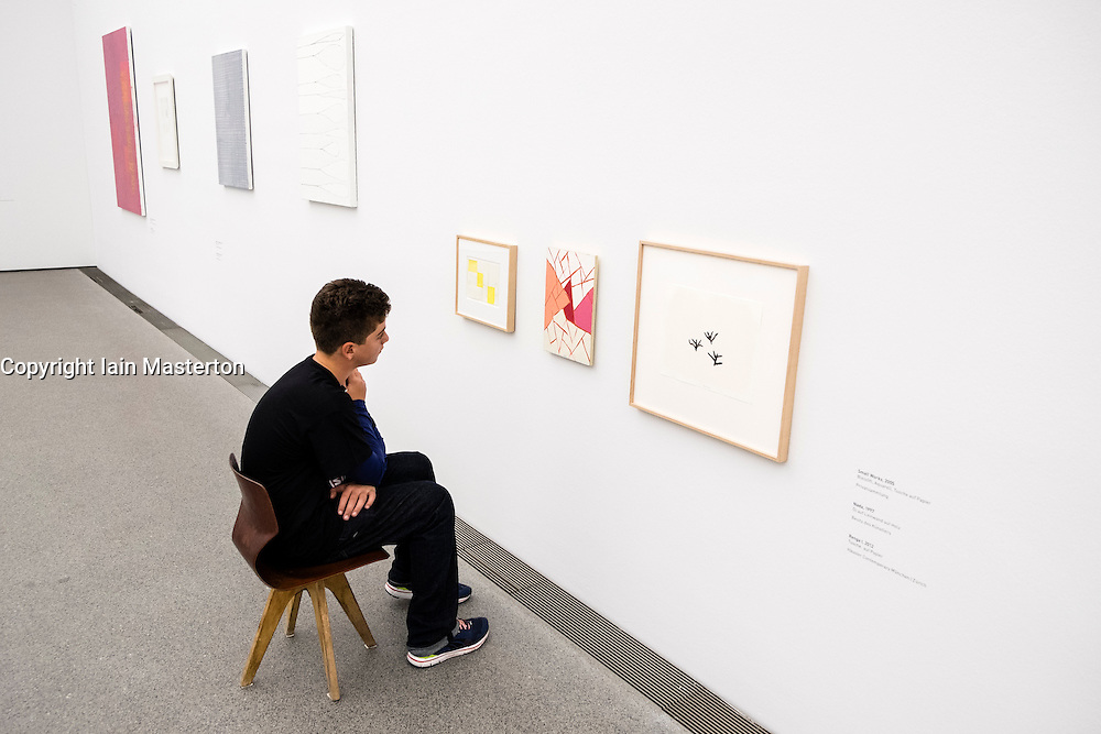 Boy looking at art works on chair provided at low level at Pinakothek Museum in Munich Germany