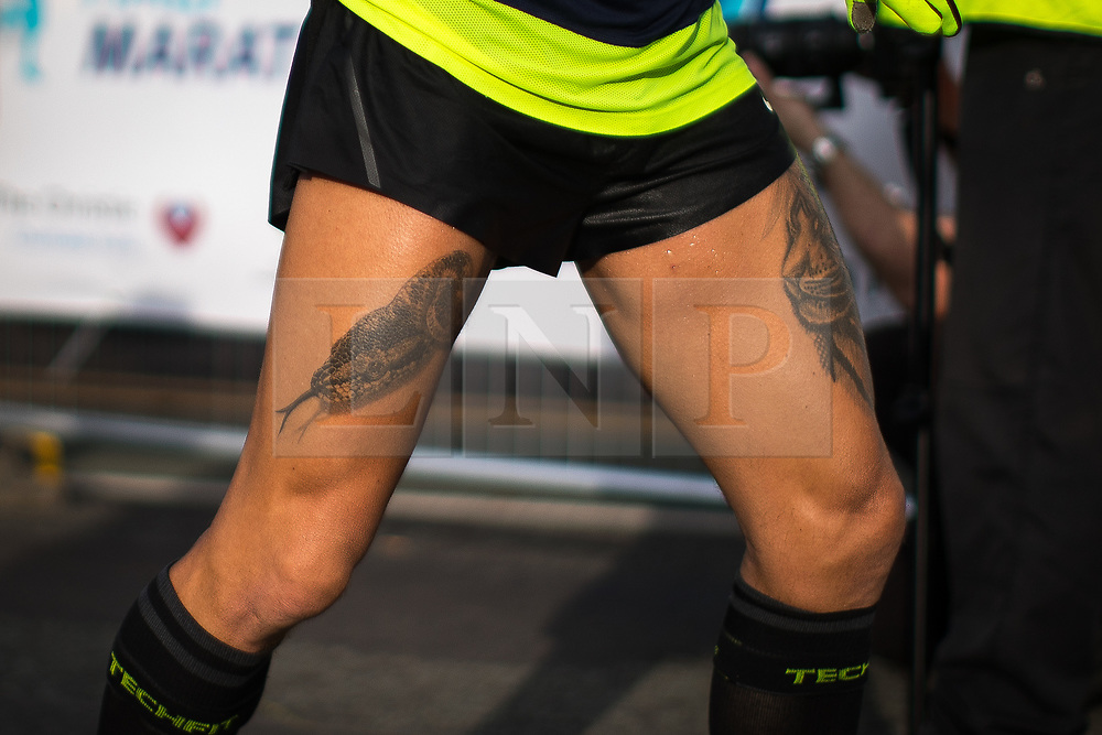 © Licensed to London News Pictures . 15/10/2017 . Manchester , UK . Athlete with a snake tattoo reaches the finish line in the Greater Manchester Half Marathon in Old Trafford . Photo credit : Joel Goodman/LNP