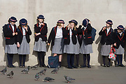 As weather warms up after a long winter, English schoolgirls visit London's Trafalgar Square. Wearing blazers and straw boater hats, the girls are standing against the wall of the National Gallery where pigeons gather hoping for crumbs. The girls are on a trip to the capital with teachers and guardians. Their cheeky expressions and behaviour describe their ages of innocence and maturing development.