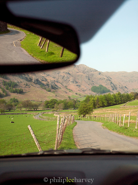 A rural road through farm land and hills in the Lake District, UK