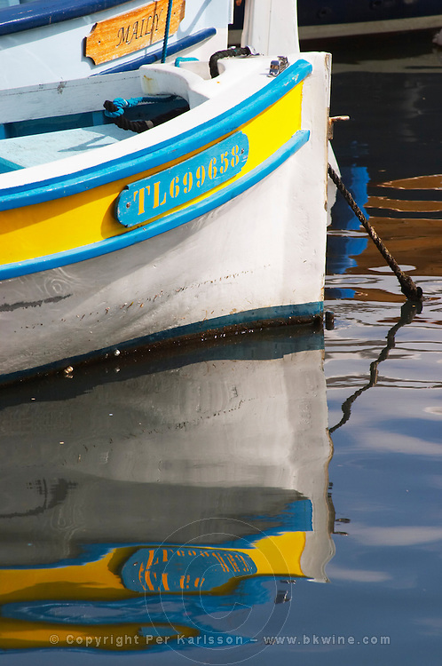 Typical Provencal fishing boats painted in bright colours white, blue, green red yellow, moored at the keyside, reflections Sanary Var Cote d'Azur France