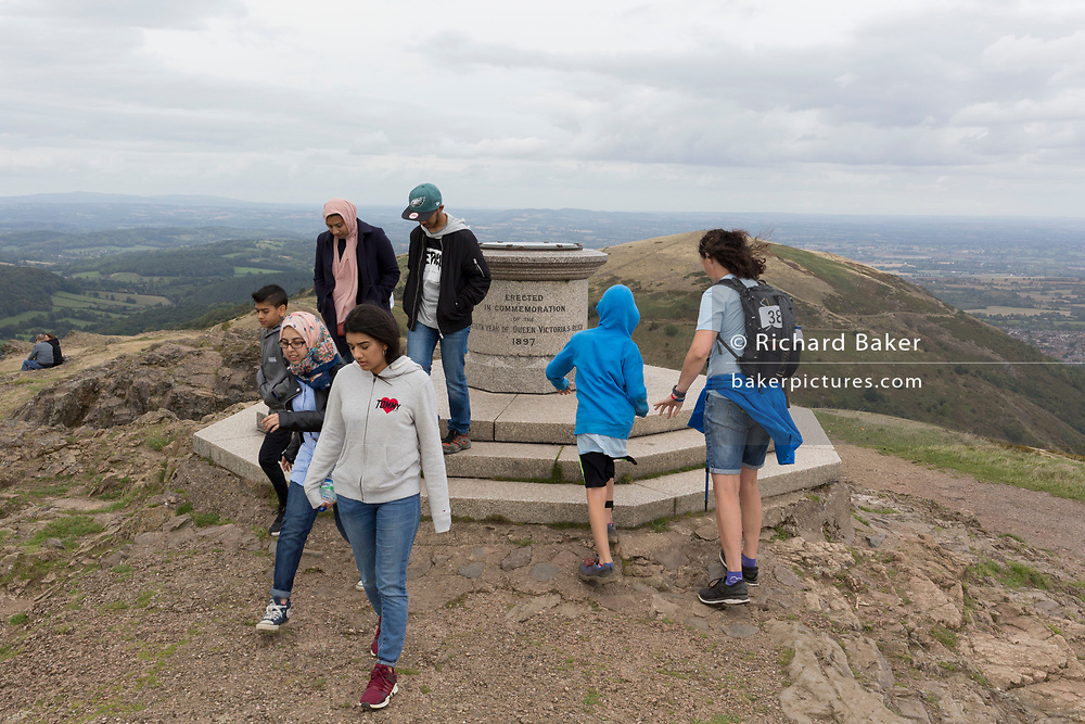 Charity walkers for Help For Heroes reach the summit of the Beacon, on 15th September 2018, in Malvern, Worcestershire, England UK. Worcestershire Beacon, also popularly known as Worcester Beacon, or locally simply as The Beacon, is a hill whose summit at 425 metres (1,394 ft)[1] is the highest point of the range of Malvern Hills that runs about 13 kilometres (8.1 mi) north-south along the Herefordshire-Worcestershire border, although Worcestershire Beacon itself lies entirely within Worcestershire.