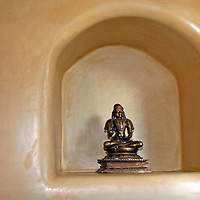 Small Buddha sits in decorative nook at the Inn of Five Graces in Santa Fe, New Mexico.