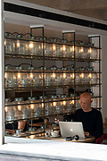 A bald man using an Apple Mac laptop computer at the Barbican Kitchen at the Barbican Centre on the 12th September in London in the United Kingdom.