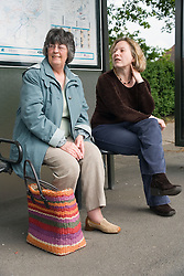 Two women waiting for a bus at a bus stop,