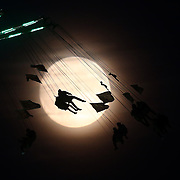 """People on a funfair ride are seen against the moon a day before the """"supermoon"""" spectacle, in London, Britain November 13, 2016 REUTERS/Neil Hall"""