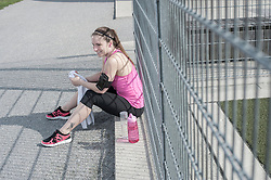 Young woman taking a break after exercising and sitting on footpath, Bavaria, Germany