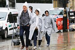 © Licensed to London News Pictures. 10/06/2019. London, UK. Tourists wearing rain ponchos as rain falls in the capital. The Met Office has just issued an amber warning for more rain, covering London and parts of southeast England later today Photo credit: Dinendra Haria/LNP