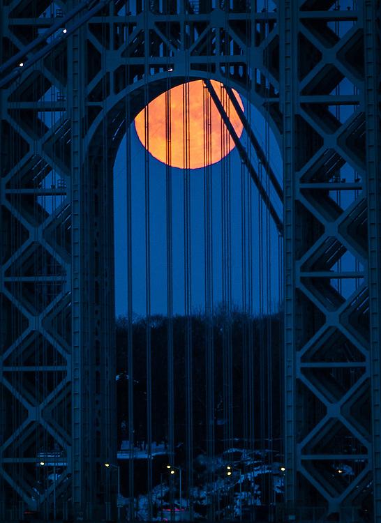 A large moon sets under the George Washington bridge at sunrise in New York City.