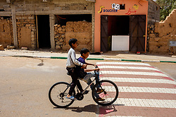 Two young boys on a bicycle passing a butchers shop in Mhamid, Morocco<br /> <br /> (c) Andrew Wilson | Edinburgh Elite media