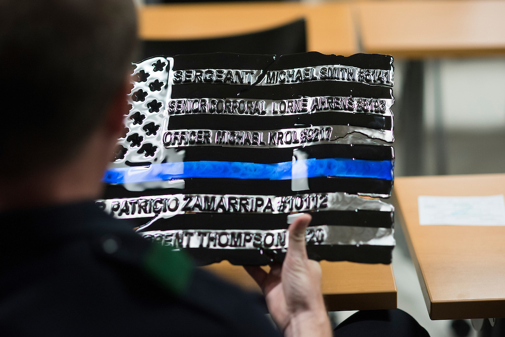 DALLAS, TX - AUGUST 11: Senior Cpl. Brian Fillingim holds a flag donated to the department showing the names of fallen officers at the Southwest Patrol Division in Dallas, Texas on August 11, 2016. (Photo by Cooper Neill for The Washington Post)