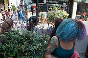 Woman with dyed blue hair and tattoos mingling with foliage in Covent Garden London, United Kingdom.