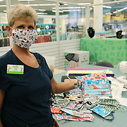 Joni Goodboe shows off face masks that were created by volunteers with donated materials from Jo-Ann fabric store  on Friday, March 27, 2020 in Orlando, Florida. Jo-Ann is providing free materials, sewing machines, workspace and guidance in their stores so that individuals can safely make gowns and masks for immediate donation to local hospitals. (Alex Menendez via AP)