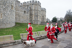 Windsor, UK. 25th November, 2018. Runners pass Windsor Castle dressed as Santa Claus and his reindeer during the 2018 Santa Dash in aid of the Alexander Devine children's hospice.