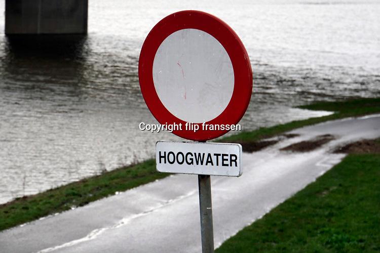 Nederland, West Maas en Waal, 26-2-2020 Het waterpeil in de rivier de Waal. Een bord waarschuwt voor het doodlopen van de weg wegens hoogwater . Foto: Flip Franssen