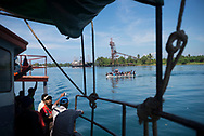 Viewed from the M.V. Thomson, a small cargo and passenger vessel sailing out of Madang Harbor, an outboard motorboat full of passengers crosses from one side of the harbor to the other in Madang, Papua New Guinea.