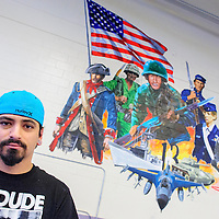 073114  Adron Gardner<br /> <br /> Artist Rudy Lopez poses for a portrait in front of his finished mural in the Miyamura High School gymnasium in Gallup Thursday.  The mural depicts a collage of American military history with the school's namesake, Hiroshi Miyamura, depicted in the center.