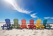 A colorful row of adirondack chairs on the beach in Florida.