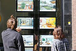 © Licensed to London News Pictures. 02/09/2020. London, UK. A couple view properties for sale in an estate agent's window. According to new figures released by Nationwide, UK houses prices were at an all-time high in August 2020 after their biggest monthly rise since 2004, as buyers took advantage of a stamp-duty holiday. The average sale price of a home jumped £3,188 to £224,123 in August. Photo credit: Dinendra Haria/LNP