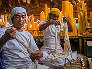 27 SEPTEMBER 2014 - BANGKOK, THAILAND: Temple attendants make wicks for prayer candles during the celebration of the Vegetarian Festival at the Chow Su Kong Shrine in Talat Noi, a Chinese enclave in Bangkok. The Vegetarian Festival is celebrated throughout Thailand. It is the Thai version of the The Nine Emperor Gods Festival, a nine-day Taoist celebration beginning on the eve of 9th lunar month of the Chinese calendar. During a period of nine days, those who are participating in the festival dress all in white and abstain from eating meat, poultry, seafood, and dairy products. Vendors and proprietors of restaurants indicate that vegetarian food is for sale by putting a yellow flag out with Thai characters for meatless written on it in red.   PHOTO BY JACK KURTZ