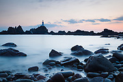 An illuminated Corbière Lighthouse at dusk on the south west coast of Jersey. A receding tide has revealed the still glistening foreground rocks. Channel Islands.