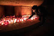"""People light candles at a makeshift memorial at Arnswalder Platz in Berlin, Germany, March 07, 2021. After 3 months the final weekly vigil has gathered at the memorial as part of the initiative """"Corona-Tote sichtbar machen"""" (lit. Make corona deaths visible) by Christian Y. Schmidt and Veronika Radulovic. Since December 6, 2020, people gather at the fountain of Arnswalder Platz every Sunday at dusk, light candles and place placards with the current death toll reported in Germany at the time. The death toll in Germany by various sources is over 72,000."""
