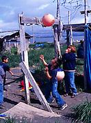 Children playing with tethered fishing floats, Yupik Eskimo village of Togiak, Alaska.