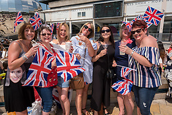 © Licensed to London News Pictures. 19/05/2018. Bristol, UK. Crowds with union jack flags in Bristol's Millennium Square celebrate the Royal Wedding of Prince Harry and Meghan Markle while watching the televised wedding on a big outdoor screen. Photo credit: Simon Chapman/LNP