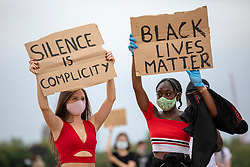"""© Licensed to London News Pictures. 03/06/2020. London, UK. Two protesters hold up signs in Hyde Park during a """"Justice for Black Lives' demonstration. Protests have taken place across the United States and in cities around the world in response to the killing of George Floyd by police officers in Minneapolis on 25 May. Photo credit: Rob Pinney/LNP"""