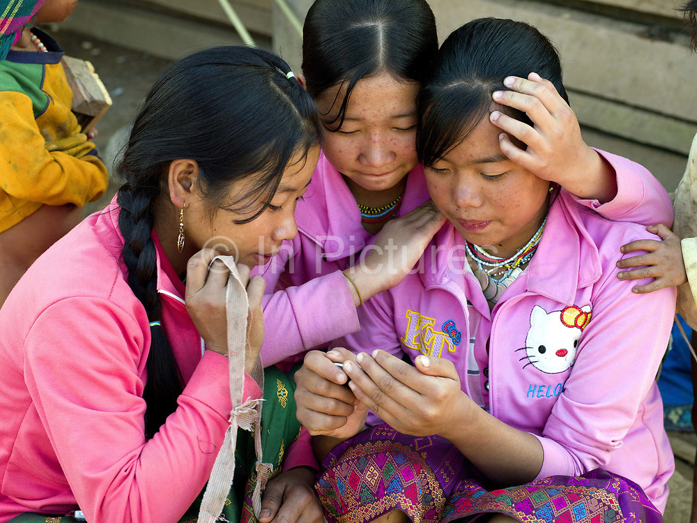 Three Akha Cherpia ethnic minority girls wearing pink Hello Kitty western style clothing watch a video on a mobile phone in Ban Nam Hin village, Phongsaly province, Lao PDR.