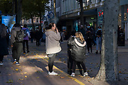 With local coronavirus lockdown measures in place and Birmingham currently set at 'Tier 2' or 'high', a woman smoking a cigarette on New Street in the city centre on 26th October 2020 in Birmingham, United Kingdom. The three tier system in the UK has levels: 'medium', which includes the rule of six, 'high', which will cover most areas under current restrictions; and 'very high' for those areas with particularly high case numbers. Meanwhile there have been calls by politicians for a 'circuit breaker' complete lockdown to be announced to help the growing spread of the Covid-19 virus.