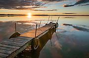 Dock at sunset reflects in Lake Mitchell, at Lakeside Charlies restaurant, near Sun-N-Snow Motel, Cadillac, Michigan, USA.