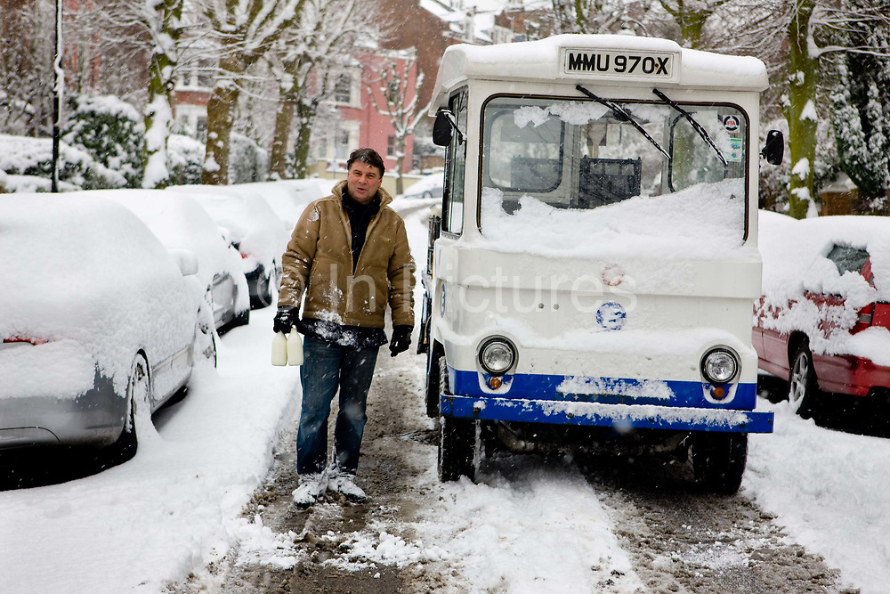 London milkman delivering on icy Highgate street covered in snow