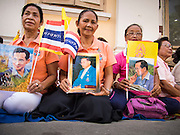 01 AUGUST 2013 - BANGKOK, THAILAND: Women with pictures of Bhumibol Adulyadej, the King of Thailand, in front of Siriraj Hospital, before the King left the hospital Thursday. The King, 85, was discharged from Bangkok's Siriraj Hospital, where he has lived since September 2009. He traveled to his residence in the seaside town of Hua Hin, about two hours drive south of Bangkok, with his wife, 80-year-old Queen Sirikit, who has also been treated in the hospital for a year.      PHOTO BY JACK KURTZ