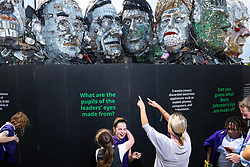 """© Licensed to London News Pictures. 21/07/2021. Stockport, UK.  Children from St Matthews C of E Primary School in Stockport visit the installation . The E7 , a Mount Rushmore-style sculpture also known as """" Mount Recyclemore """" , is unveiled outside the Stockport headquarters of recommerce company musicMagpie , who commissioned the sculpture for the G7 summit in June to much media interest . The sculpture was created out of e-waste in the likeness of the G7 leaders by artist and founder of the Mutoid Waste Company, Joe Rush , and will serve as an educational attraction during events hosted this summer , in collaboration with Totally Stockport and Stockport Council . Photo credit: Joel Goodman/LNP"""