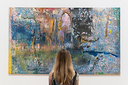 """© Licensed to London News Pictures. 30/05/2019. LONDON, UK. A staff member poses next to """"Towards Crab Island"""", 1983, by Frank Bowling at a preview of works by artist Frank Bowling (born in Guyana in 1934).  The retrospective exhibition spans his six-decade career and takes place 31 May to 26 August 2019 at Tate Britain.  Photo credit: Stephen Chung/LNP"""