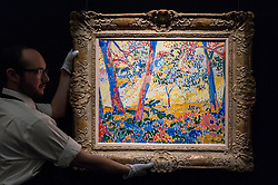 "© Licensed to London News Pictures. 08/04/2016. London, UK. A Sotheby's technician shows Maurice De Vlaminck's ""Sous-Bois"", 1905, est. $12-18million.  Sotheby's auction preview, at their New Bond Street gallery, of works to be in the upcoming New York Impressionist, modern and contemporary art sale. Photo credit : Stephen Chung/LNP"