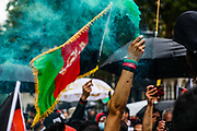 """An Afghan man carries a green flare and a bracelet with the Afghan national flag during a protest """"Save Afghanistan"""" to protest the resurgence of the Taliban outside Downing Street, Britain's PM Office in central London on Saturday, Aug 21, 2021. (VX Photo/ Vudi Xhymshiti)"""