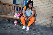 Woman in orange leggings sitting smoking a cigarette on a bench outside a hospital in London, UK. Her general demeanor was of someone who was troubled or unhappy with her situation.