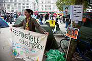 "Spanish protester with her sign asking fro responsible consumption. Occupy London protest at St Pauls, October 16th 2011. Protest spreads from the US with this demonstrations in London and other cities worldwide. The 'Occupy' movement is spreading via social media. After four weeks of focus on the Wall Street protest, the campaign against the global banking industry started in the UK this weekend, with the biggest event aiming to ""occupy"" the London Stock Exchange. The protests have been organised on social media pages that between them have picked up more than 15,000 followers. Campaigners gathered outside  at midday before marching the short distance to Paternoster Square, home of the Stock Exchange and other banks.It is one of a series of events planned around the UK as part of a global day of action, with 800-plus protests promised so far worldwide.Paternoster Square is a private development, giving police more powers to not allow protesters or activists inside."